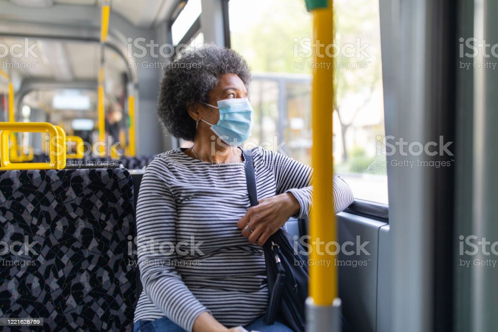 Woman with face mask travelling in the tram during Covid-19 outbreak Woman wearing medical face mask commuting in a tram train during corona virus outbreak. Female travelling in metro during Covid-19 pandemic. Accidents and Disasters Stock Photo