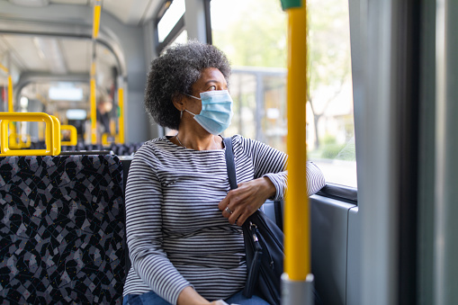 Woman wearing medical face mask commuting in a tram train during corona virus outbreak. Female travelling in metro during Covid-19 pandemic.