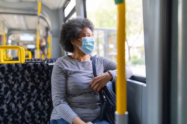Woman with face mask travelling in the tram during Covid-19 outbreak stock photo