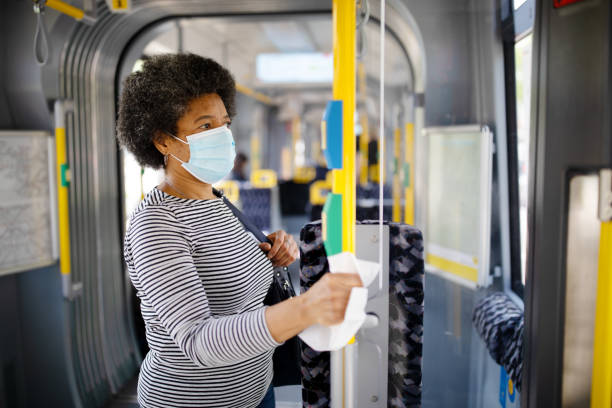 Woman with face mask travelling in tram during Covid-19 outbreak stock photo