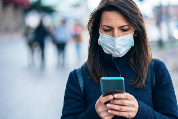 Woman with face protective mask Portrait of young woman on the street wearing  face protective mask to prevent Coronavirus and anti-smog and using smartphone pathogen stock pictures, royalty-free photos & images