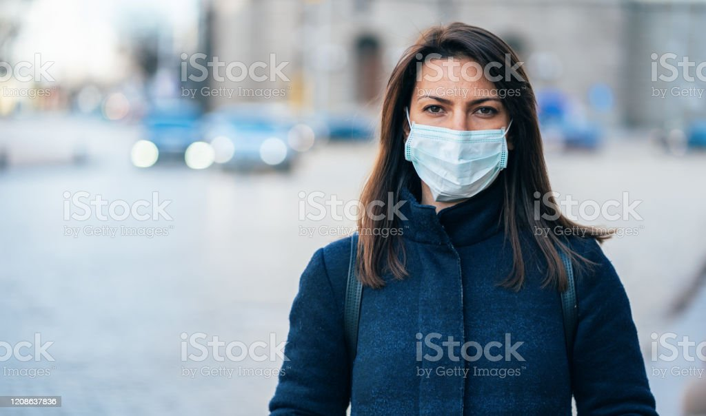 Woman with face protective mask Portrait of young woman on the street wearing  face protective mask to prevent Coronavirus and anti-smog Adult Stock Photo