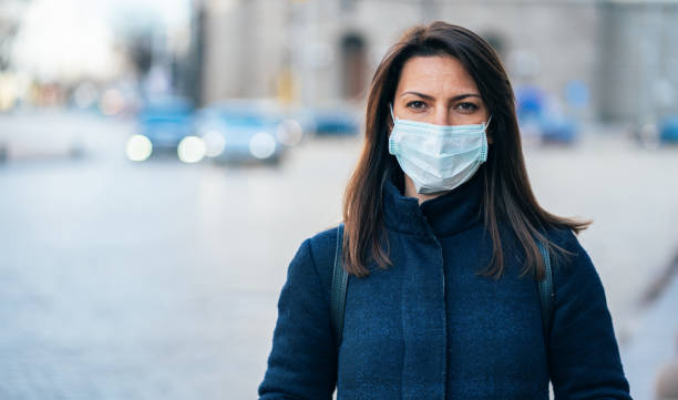 Woman with face protective mask Portrait of young woman on the street wearing  face protective mask to prevent Coronavirus and anti-smog covid mask stock pictures, royalty-free photos & images