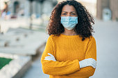 Portrait of young woman on the street wearing face protective mask to prevent Coronavirus