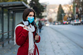 Portrait of young woman on the street wearing face protective mask to prevent Coronavirus and anti-smog and using tablet for navigation