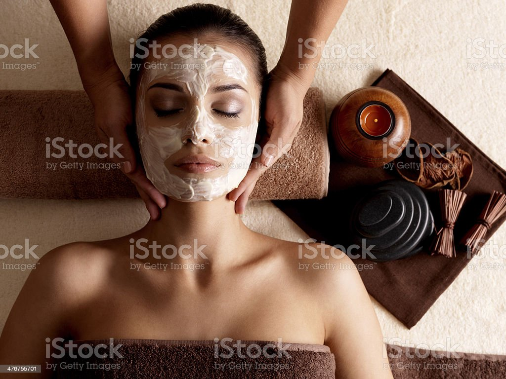 Woman with facial mask getting massage at spa stock photo