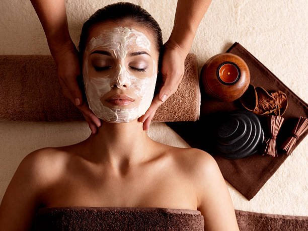 woman with facial mask getting massage at spa - spa treatment stock photos and pictures