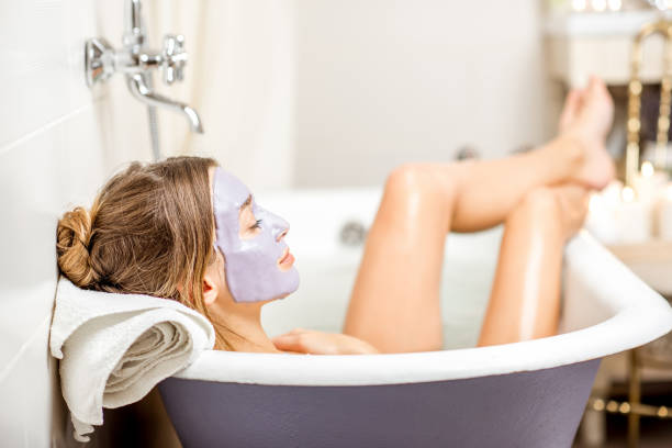 Woman with facial mask in the bathroom - foto stock