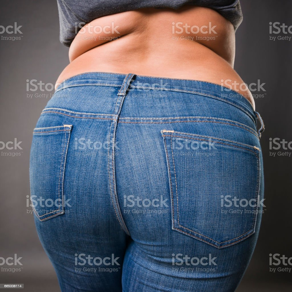 Woman with fat buttocks in blue jeans, overweight female body closeup stock photo