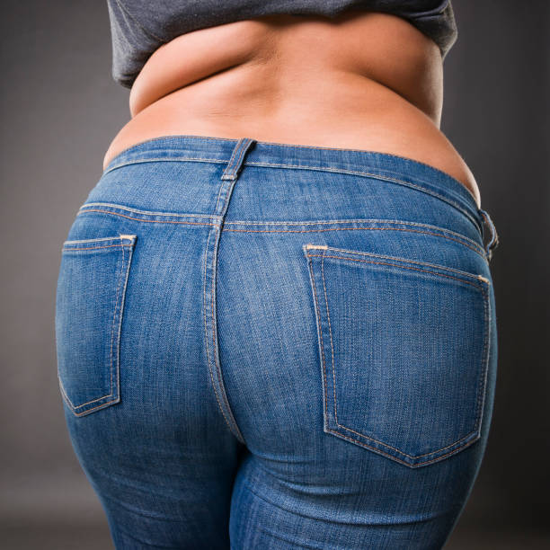 woman with fat buttocks in blue jeans, overweight female body closeup - buttock stock photos and pictures
