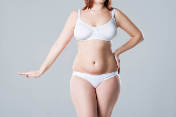Woman with fat flabby belly, overweight female body on gray background stock photo