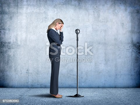 A businesswoman sheepishly places her head in her hand as she steps up to a microphone and exhibits her fear of public speaking.