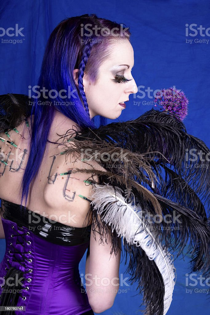 Woman with feather wings in profile enjoying flower. stock photo