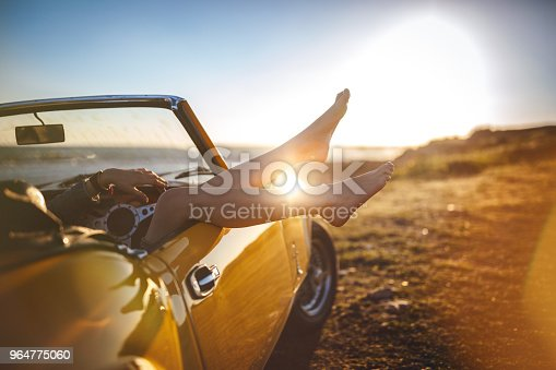 Woman on road trip relaxing at beach lying down in retro convertible car at sunset