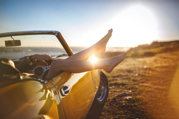 Woman with feet sticking out convertible car relaxing on holidays stock photo