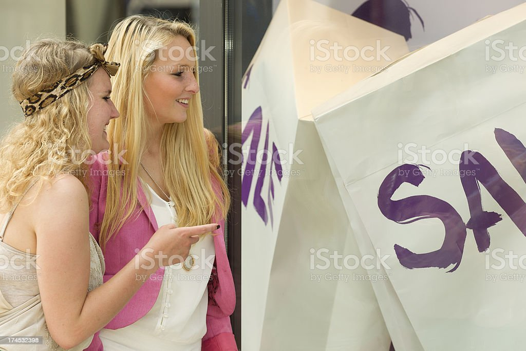 Woman With Female Friend Pointing At Sale Sign On Display royalty-free stock photo