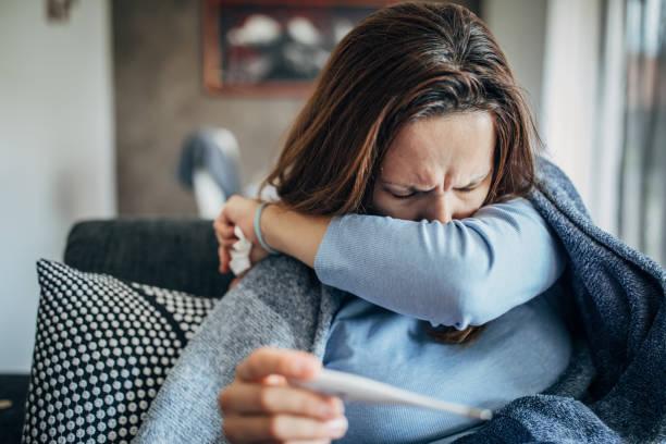 frau mit fiebersymptomen sitzt auf sofa und hält thermometer - erkältung und grippe stock-fotos und bilder