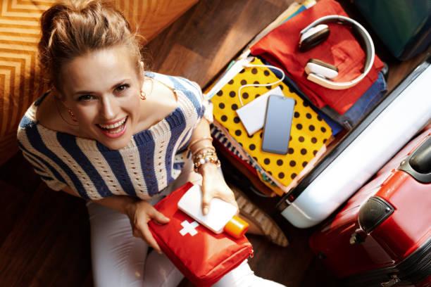 Frau mit Erste-Hilfe-Kit im modernen Haus am sonnigen Sommertag – Foto
