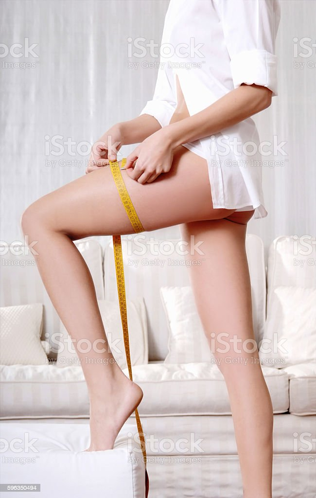 woman with fitness body and measuring tape at home Lizenzfreies stock-foto