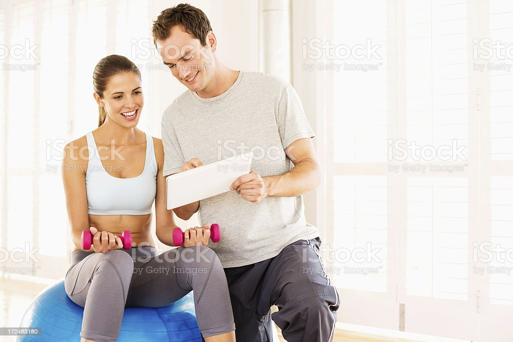 Woman With Fitness Trainer Looking At Exercise Plan royalty-free stock photo