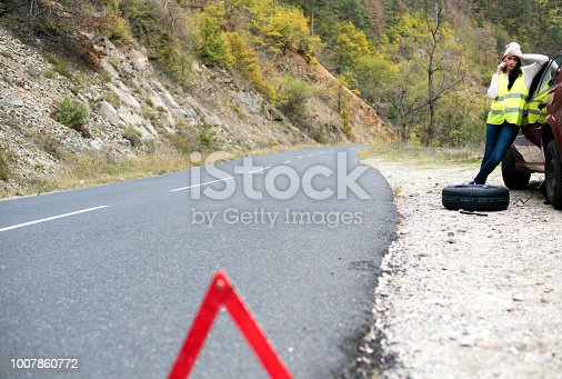 627511482 istock photo Woman with flat tire calling for help 1007860772