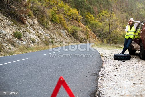104275470istockphoto Woman with flat tire calling for help 891373568