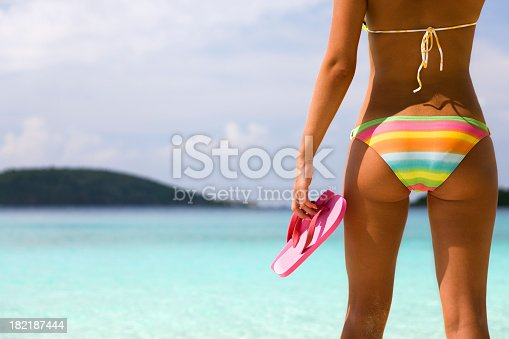istock woman with flip flops on a beach 182187444