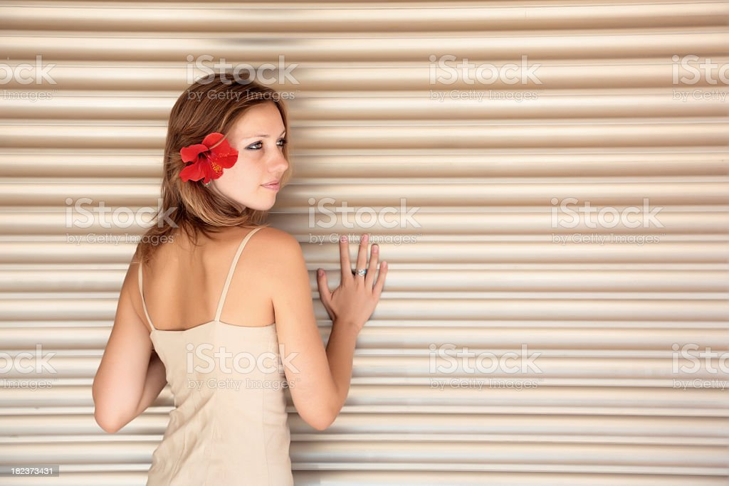 Woman with flower in her hair stands near the wall stock photo