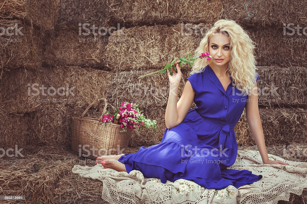Woman with flower sitting on the hay. stock photo