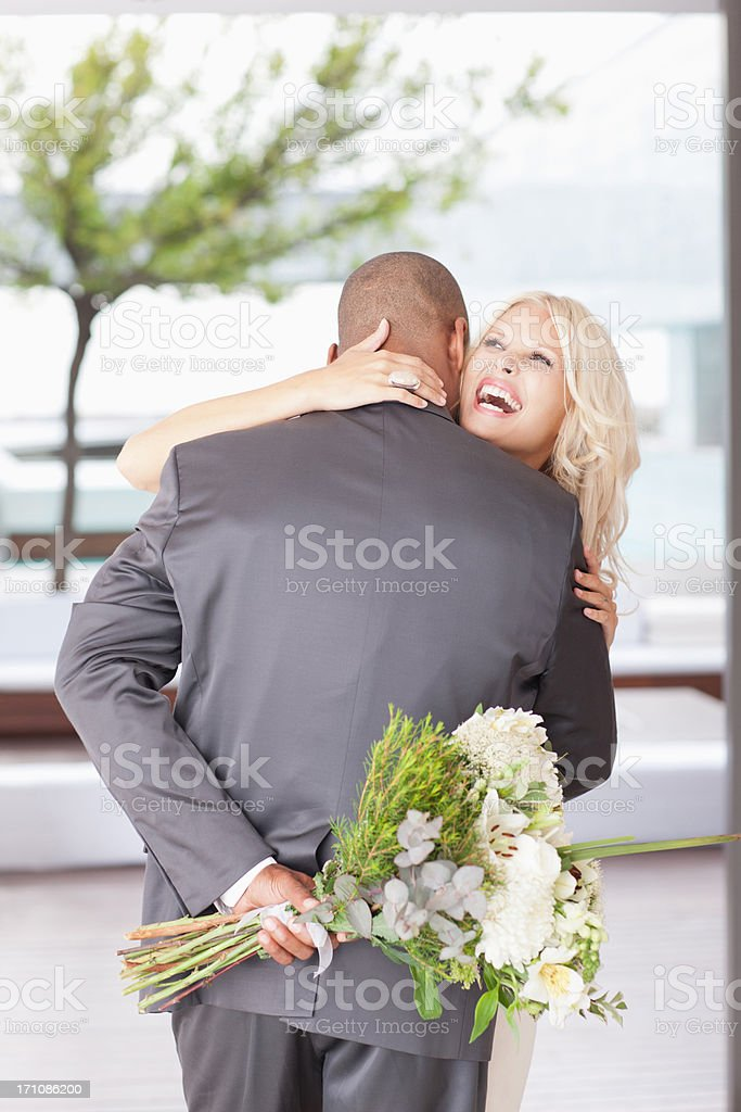 Woman with flowers hugging man stock photo