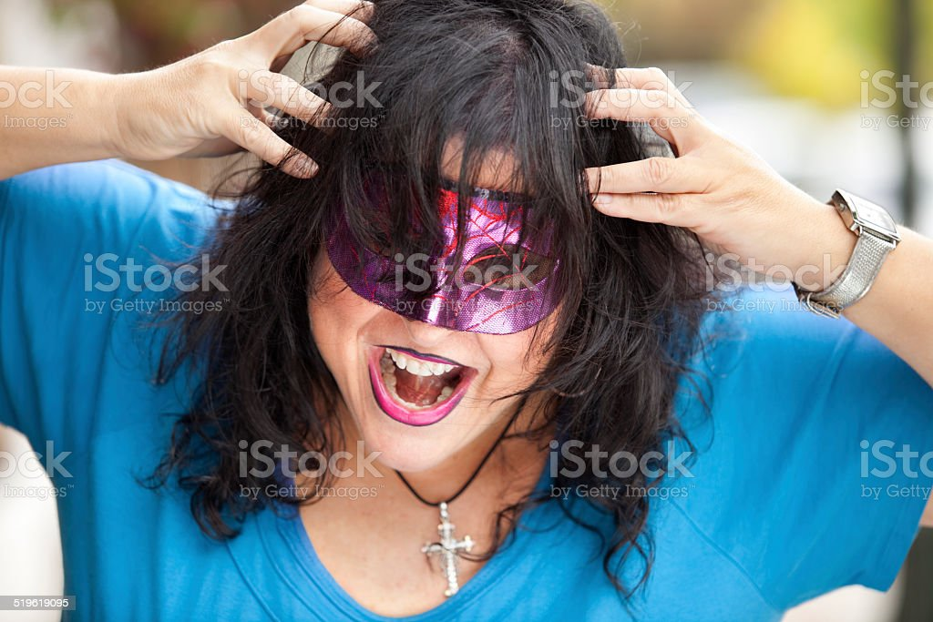 Woman with fly away hair and mask Freaking Out stock photo