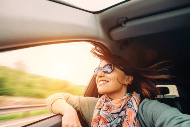 Woman with flying hair looks from car window stock photo
