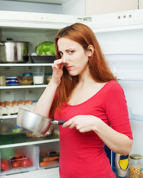 woman  with foul food  near refrigerator Long-haired  woman  in red holding  nose because of bad smell near fridge at home addle stock pictures, royalty-free photos & images