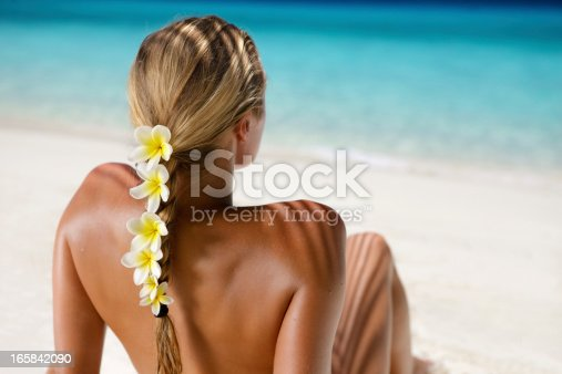 istock woman with frangipani in hair sunbathing at the Caribbean beach 165842090