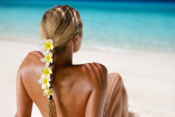 woman with frangipani in hair sunbathing at the Caribbean beach stock photo