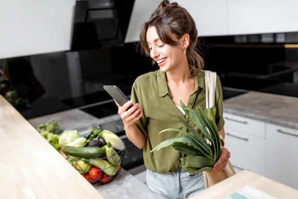 Woman with fresh groceries on the kitchen at home stock photo