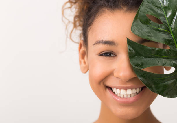 Woman with fresh leaf covering half of face African-american woman with fresh leaf covering half of face on white background with copy space peel plant part stock pictures, royalty-free photos & images