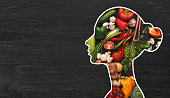 Food for health. Woman silhouette with fresh vegetables in her body on wooden background with copy space, panorama