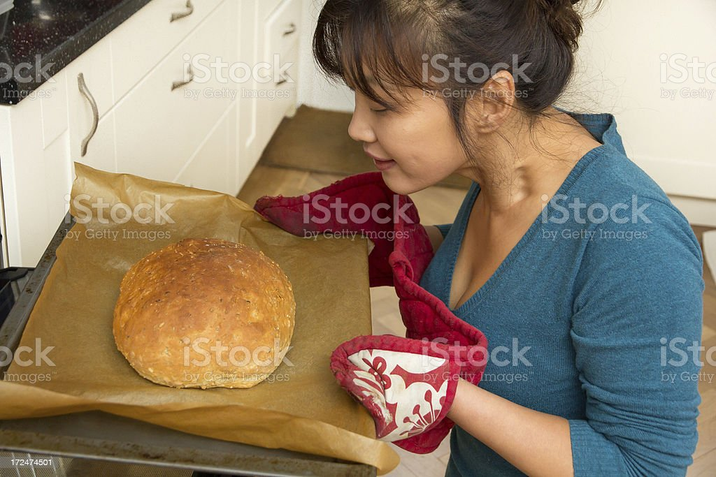 Woman with freshly baked bread from oven stock photo