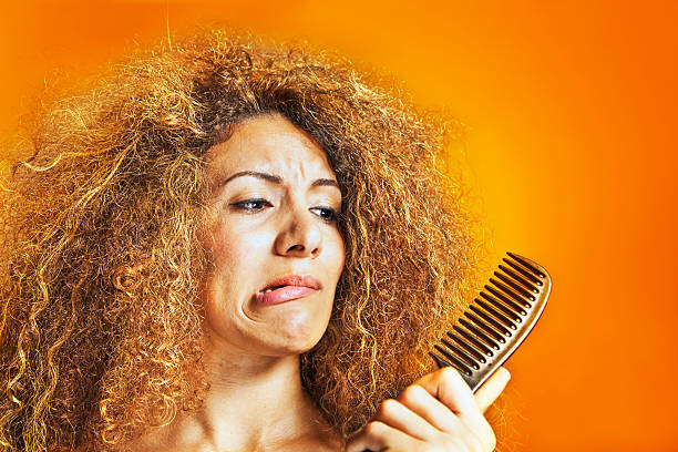woman with frizzy and curly hair looking at a comb - messy hair stock photos and pictures
