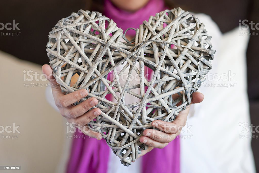 Woman with fuchsia scarf by offering a rustic heart. royalty-free stock photo
