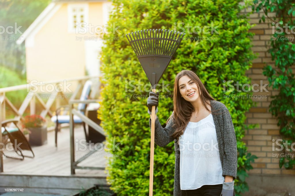 Smiling young woman with garden leaf rake in her home backyard with...