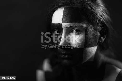 Young woman with geometric black and white face painting.