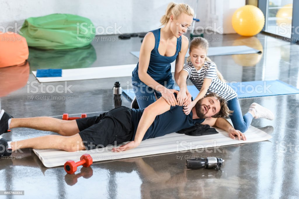 Woman with girl helping tired man lying on mat at gym royalty-free stock photo