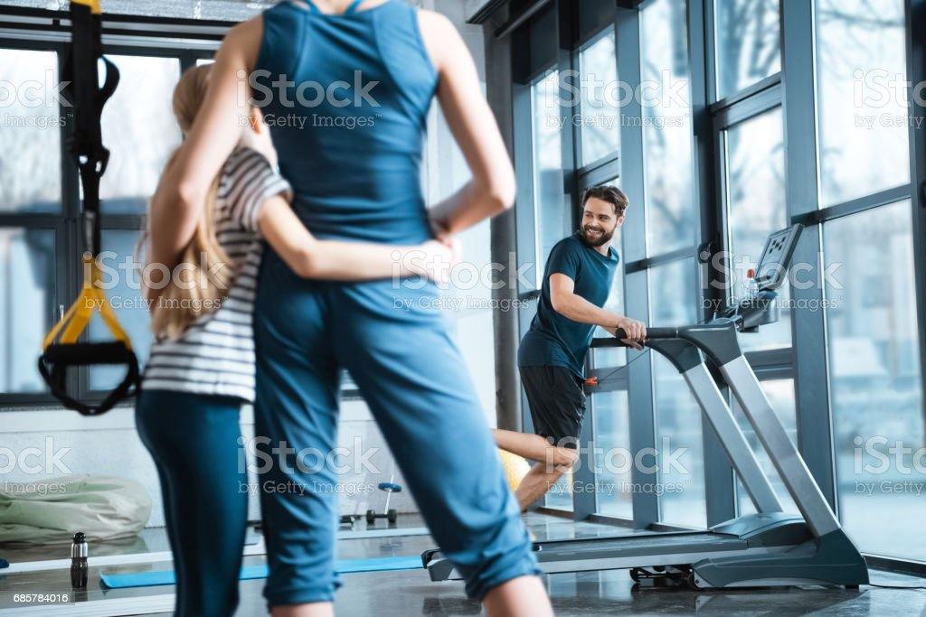Woman with girl looking at handsome man workout on treadmill at gym royalty-free stock photo