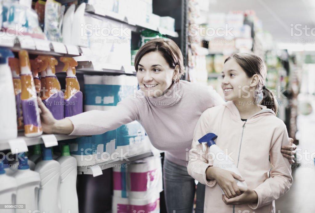 Mujer con niña en busca de productos de limpieza en supermercado - Foto de stock de Adolescente libre de derechos