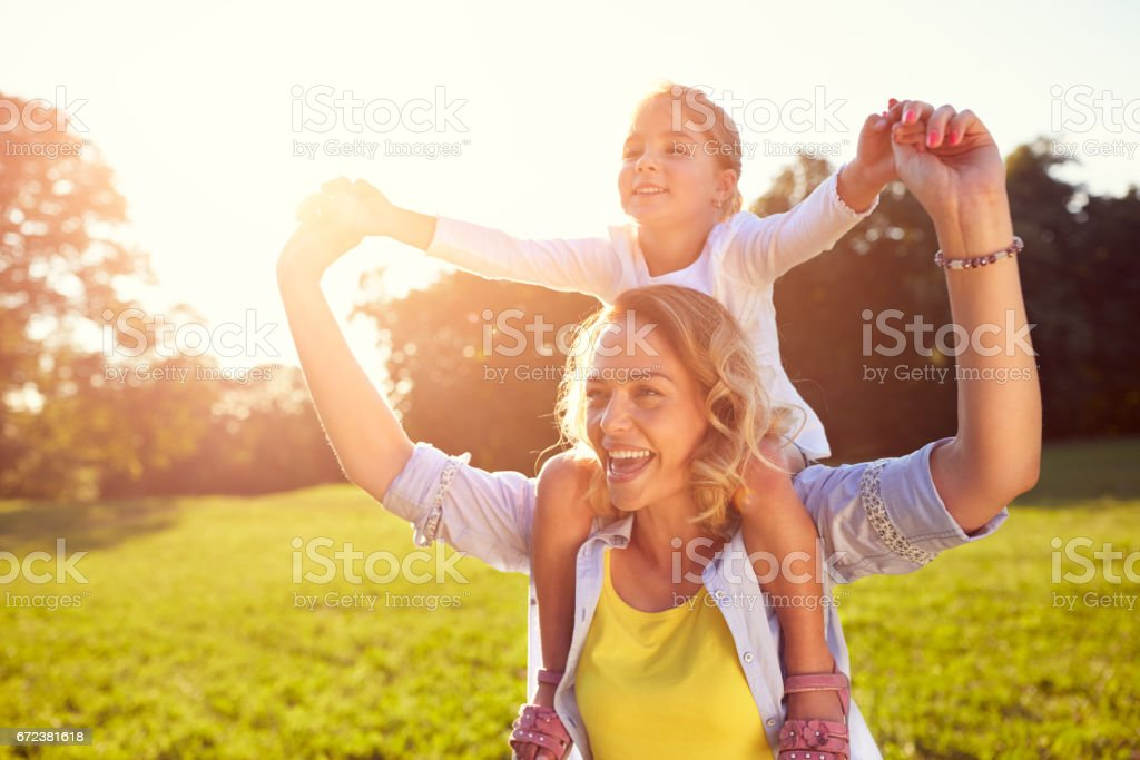 Woman with girl on shoulders stock photo