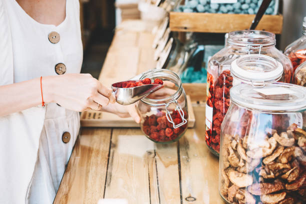 Woman with glass jars buying dried berries and fruits in zero waste shop. stock photo
