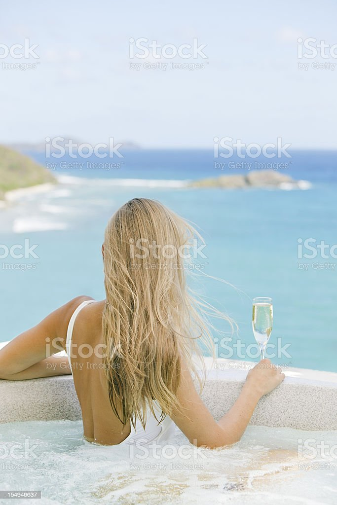 woman with glass of champagne soaking in a jacuzzi whirlpool royalty-free stock photo