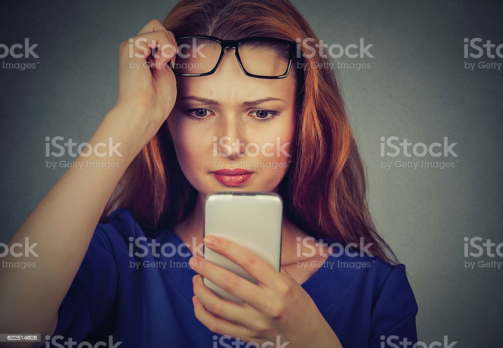 woman with glasses having trouble seeing cellphone vision problems stock photo